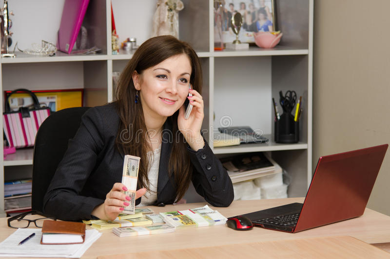 Girl holding a wad of money and talking on phone in office. Cute business woman in the office at the computer royalty free stock image