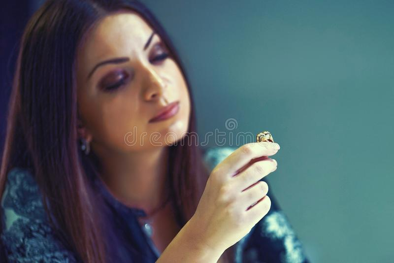 A girl holding a wedding ring doubtfully. Woman holding wedding engagement ring in hands, engaged girl doubts about marriage proposal, abandoned wife depressed royalty free stock photography