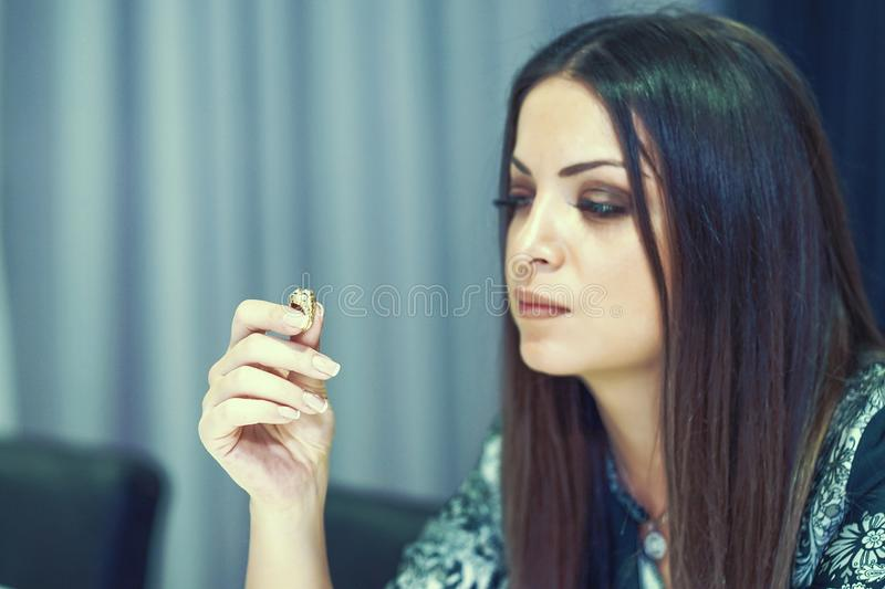 A girl holding a wedding ring doubtfully. Woman holding wedding engagement ring in hands, engaged girl doubts about marriage proposal, abandoned wife depressed royalty free stock image