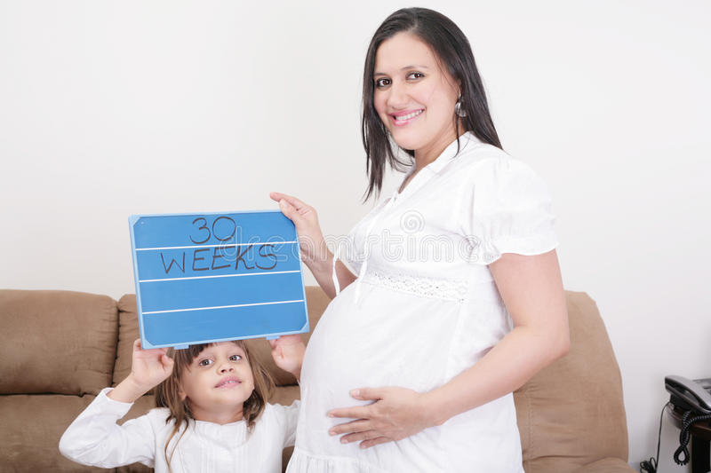 Girl holding a 30 weeks sign to her expectant mother stock photos