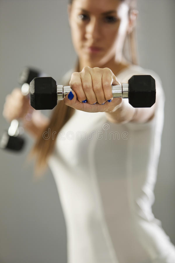 Girl holding weights in her hands royalty free stock photography