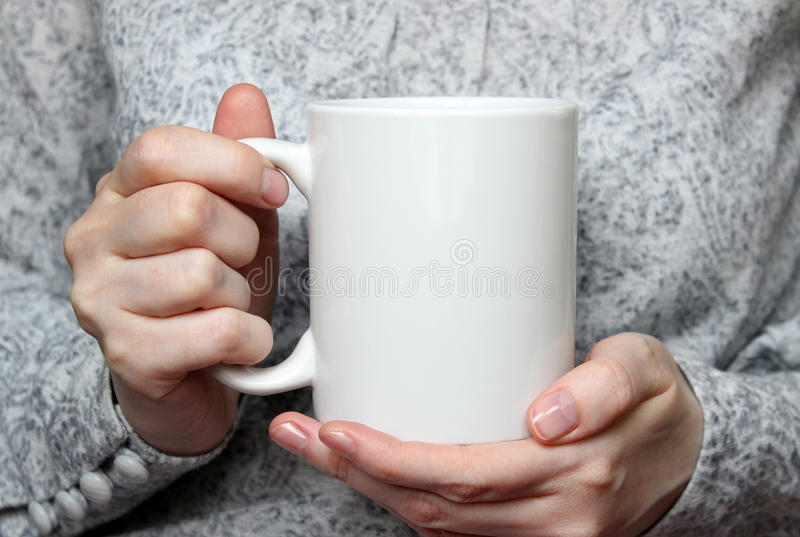 Girl is holding white cup in hands. White mug in woman's hands. stock photo