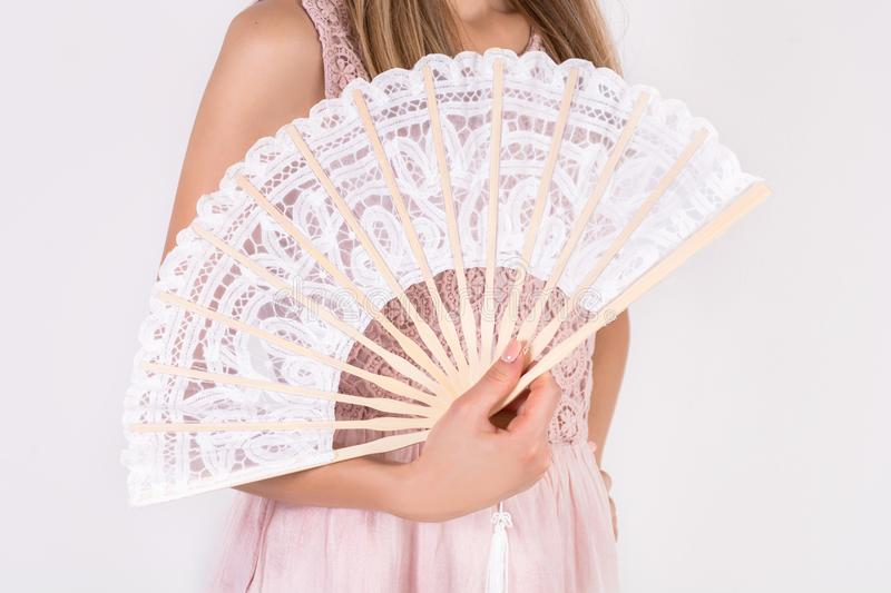 Girl holding white lace folding wedding hand fan in hand. Young beautiful fashion model woman holding white lace folding wedding hand fan in hand isolated on stock photography