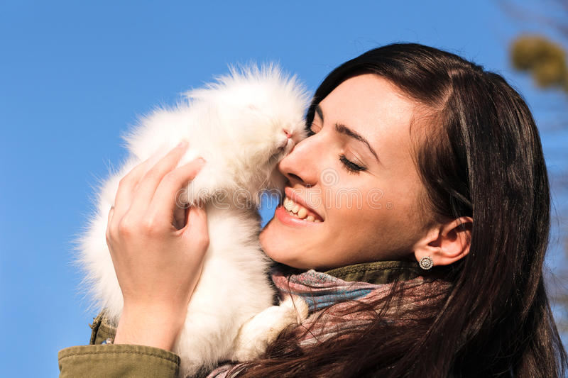 Girl holding a white little rabbit stock photography
