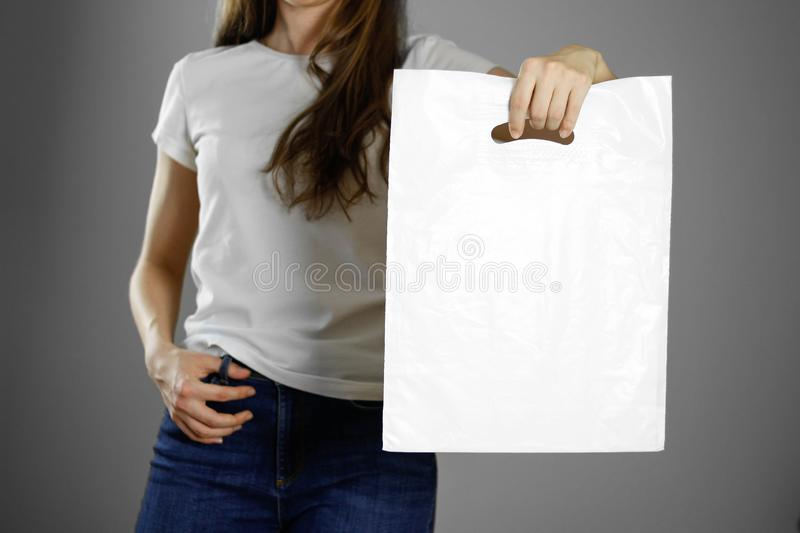Girl holding a white plastic bag. Close up. Isolated background royalty free stock photography