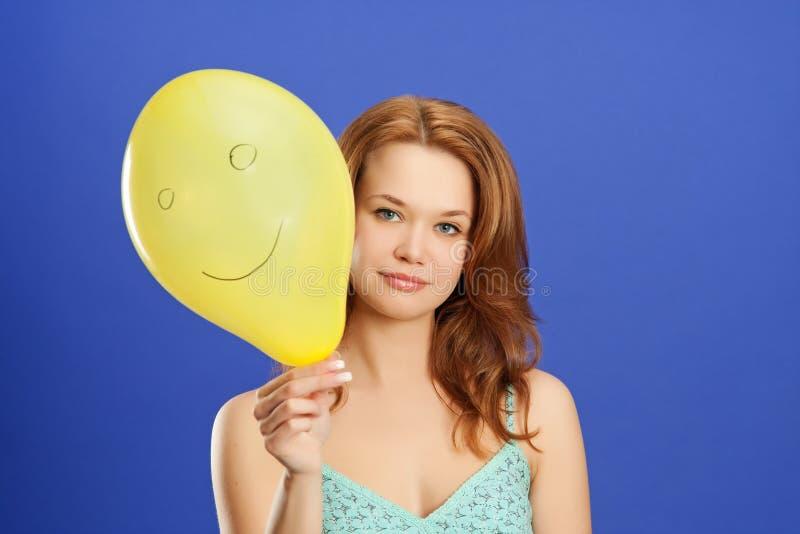 Girl holding yellow smiling balloon stock photos
