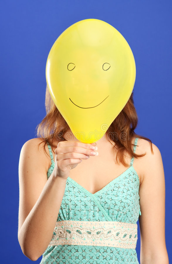 Girl holding yellow smiling balloon close up stock image