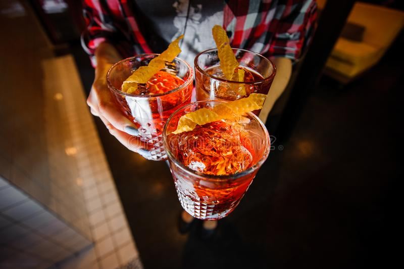 Girl holds alcoholic cocktails negroni with ice and dried honeycombs. Elegant girl in a bar holds three alcoholic cocktails negroni of amber color with ice and royalty free stock photo