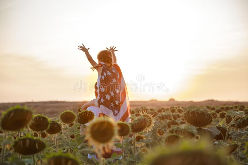 A girl holds an American flag at sunset. A little girl holds an American flag on her shoulders, at sunset in a beautiful field. Patriotic feeling royalty free stock images