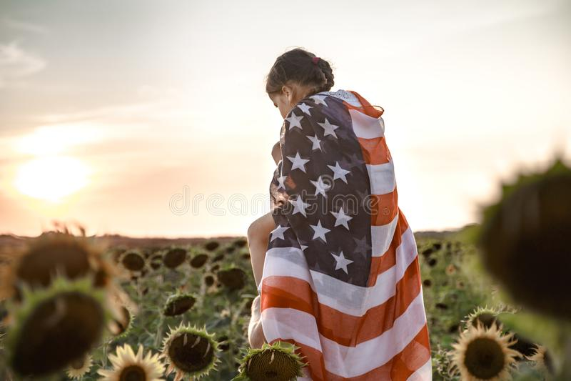 A girl holds an American flag at sunset. A little girl holds an American flag on her shoulders, at sunset in a beautiful field. Patriotic feeling stock photography