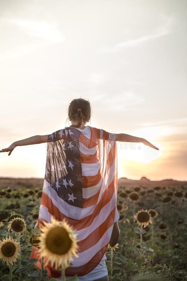 A girl holds an American flag at sunset. A little girl holds an American flag on her shoulders, at sunset in a beautiful field. Patriotic feeling stock image