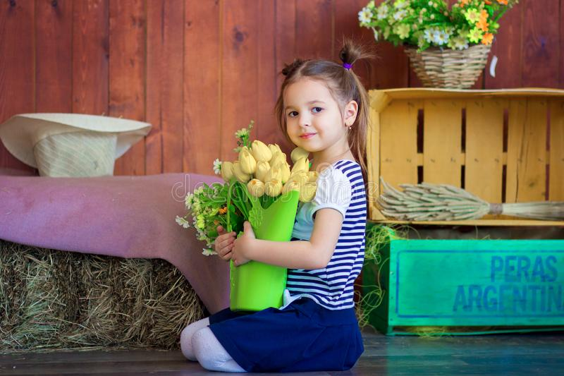 The girl holds a basket with yellow tulips. Easter spring decor of the room stock photography