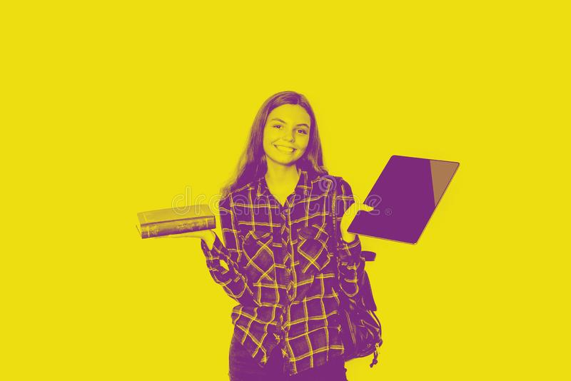 Girl holds book and tablet in her hands. BAck to school. duotone yellow and violet stock photos