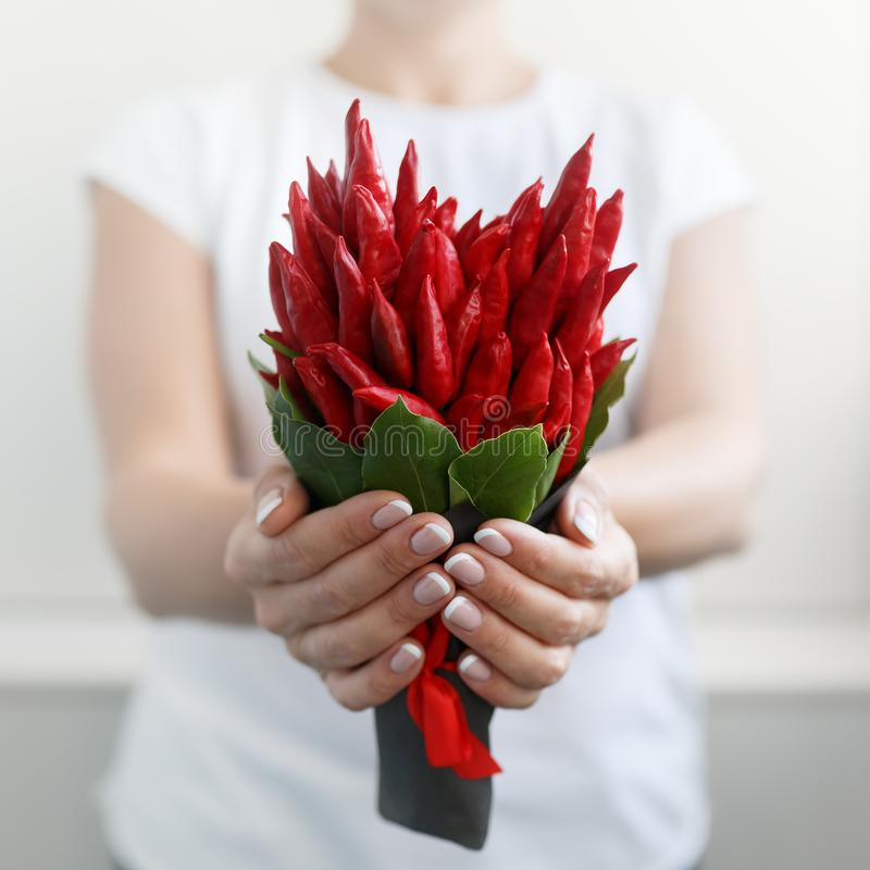 Girl holds by both hands a small bouquet made of red hot pepper in the shape of a heart royalty free stock photos