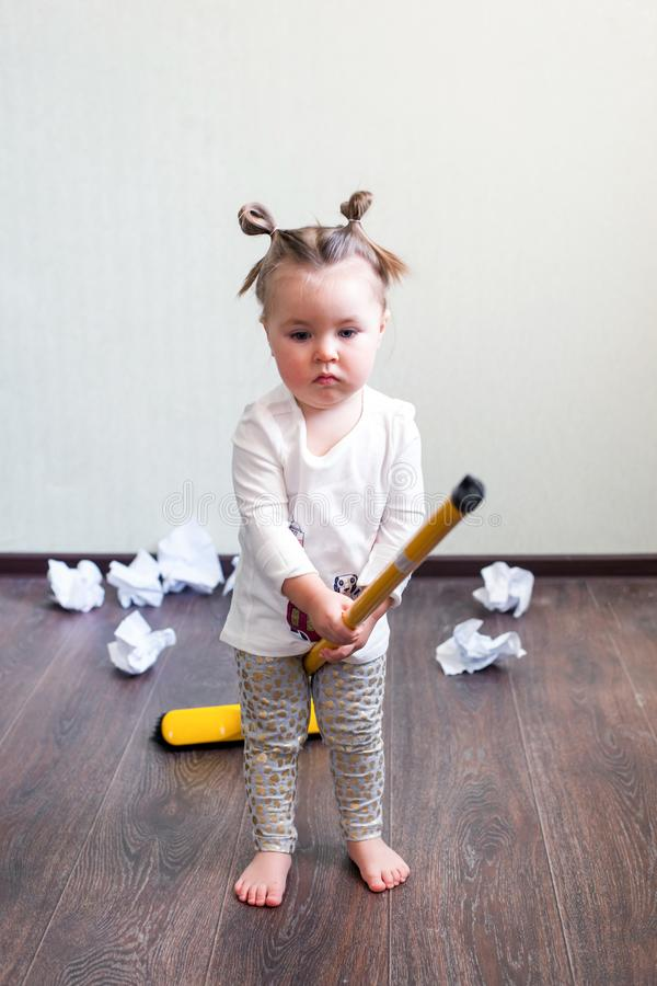 A girl holds a broom for 1.5 years, the concept of house cleaning, cleaning company, cleaning space, minimalism. A girl holds a broom for 1.5 years, the concept stock images