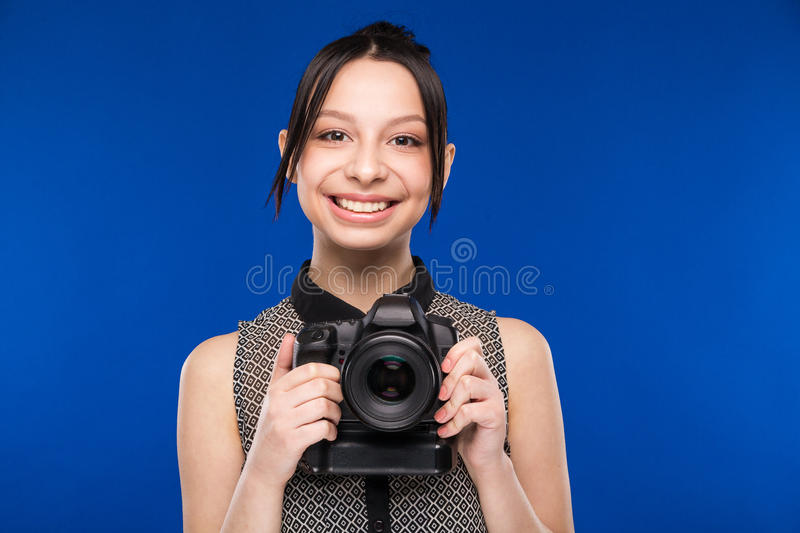 Girl holds the camera in hands. On a blue background stock images