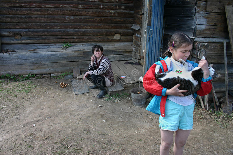 Girl holds a cat, near farmhouse, countryside, Russia. royalty free stock photography
