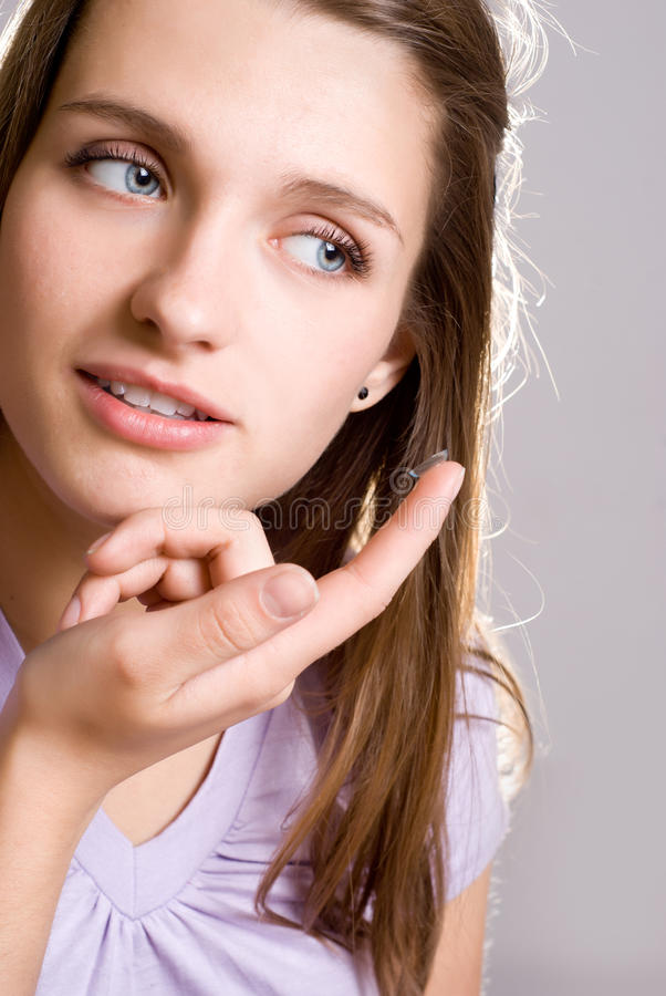 A girl holds a contact lens stock photos