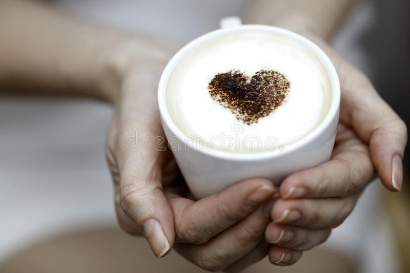 The girl holds a cup of coffee with heart from cinnamon stock photos