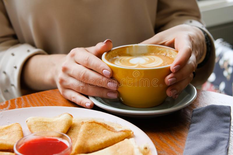 The girl holds a Cup of coffee on a wooden table in the cafe. Next to a plate of pancakes and jam. Coffee break, Breakfast. The. Concept of power. Close up stock images