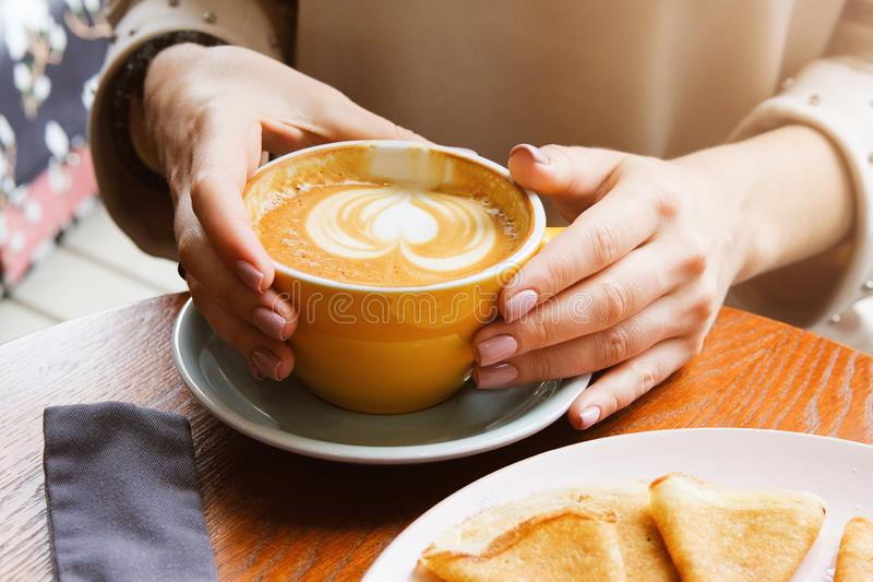 The girl holds a Cup of coffee on a wooden table in the cafe. Next to a plate of pancakes and jam. Coffee break, Breakfast. The. Concept of power. Close up stock photos