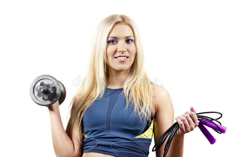 Girl holds a dumbbell, and jump rope royalty free stock photo