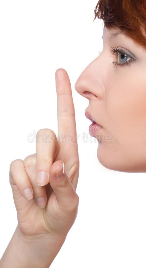 A girl holds a finger to lips gesture silently. Over white background royalty free stock images