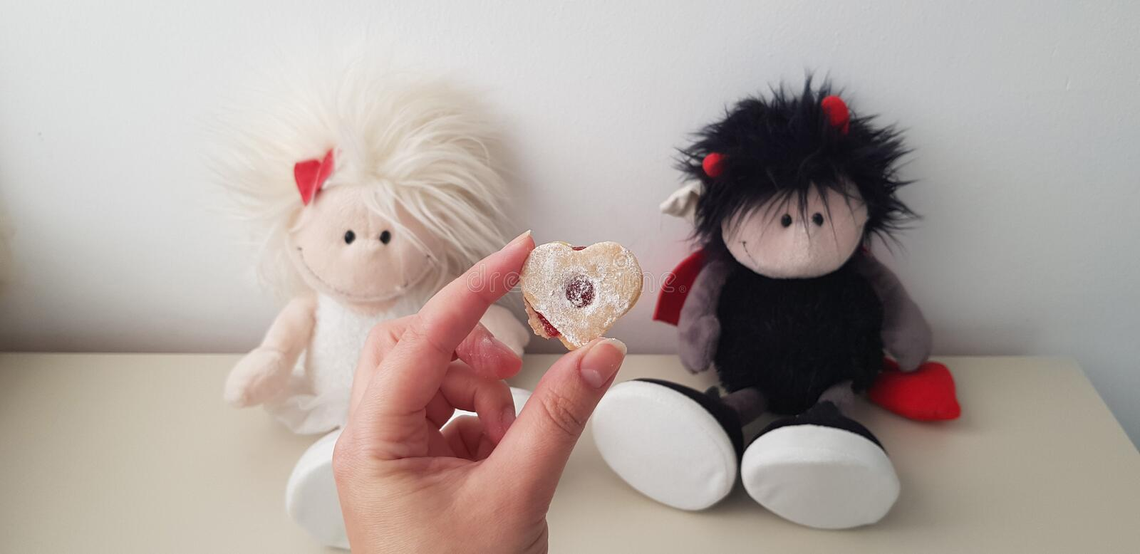 Cookie with red filling against twin angel and demon romantic toys stock photo