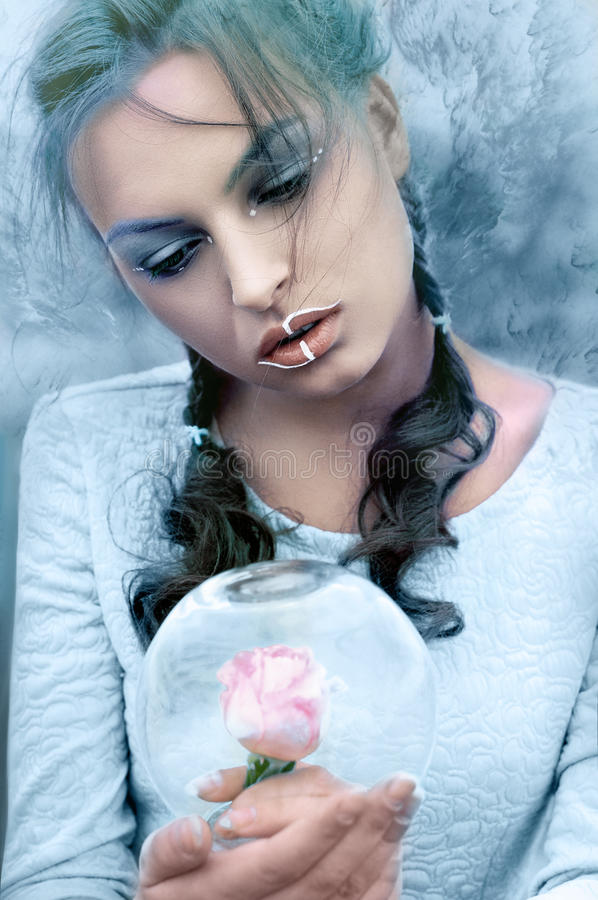 Girl holds a glass flask in the frost with a rose inside stock photos