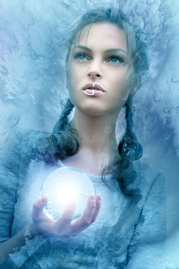 Girl holds a glass glowing sphere royalty free stock photo