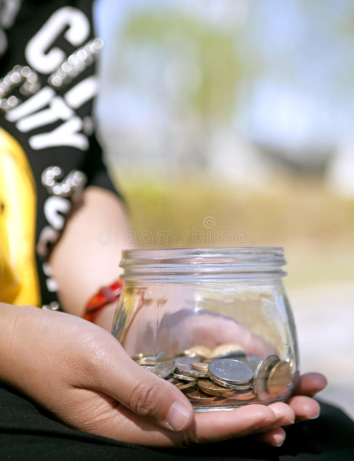 A girl holds a glass jar with chinese coins stock photo