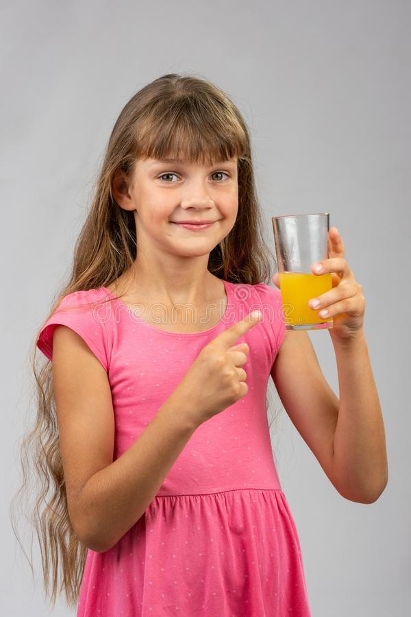 A girl holds a glass of orange juice in her hand and points her finger at it. A girl holds a glass of orange juice in her hand and points her finger at  it royalty free stock images