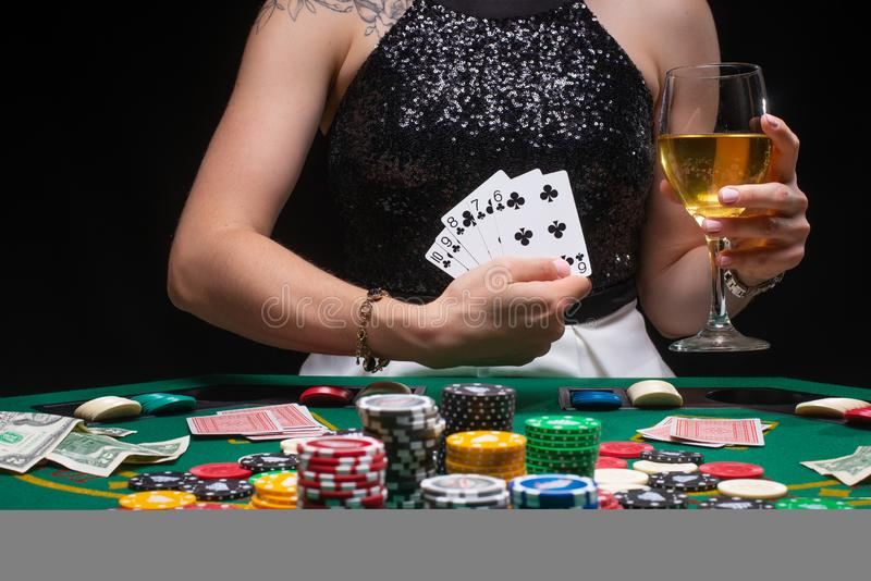 Girl holds a glass of wine. Poker player shows a winning combination in cards against the background of chips, money. Concept of a. Casino, gaming hall, winners royalty free stock photos