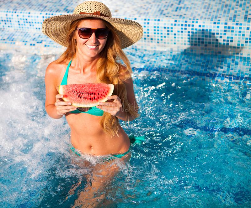 A girl holds half a red watermelon over a blue pool, relaxing o royalty free stock photography