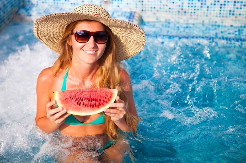 A girl holds half a red watermelon over a blue pool, relaxing o royalty free stock images