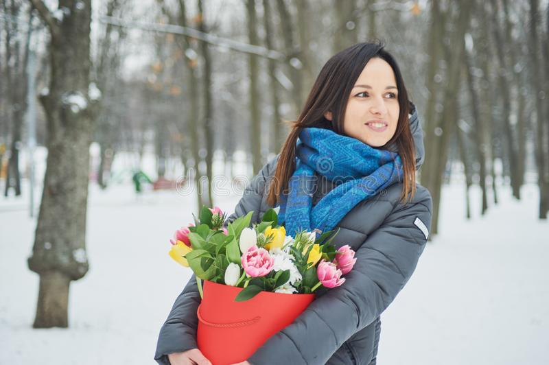 Girl holds in hands red gift box with beautiful bouquet of blooming pink, yellow and white tulips and white chrysanthemums Flowers. As a gift for Women& x27;s stock photo