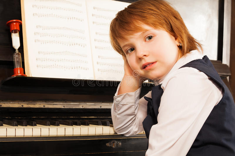 Girl holds her face with hand on the piano. Small girl in school uniform holds her face with hand on the piano during lesson indoors stock photo