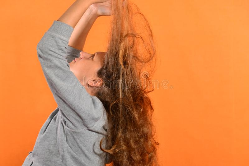 The girl holds her hair up and they bloom on the fly on a yellow background.  royalty free stock photography