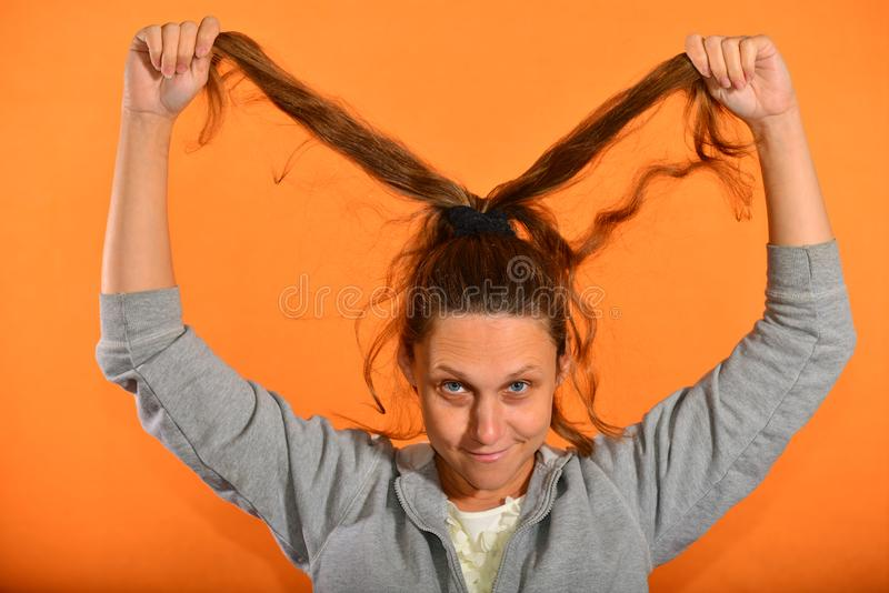 The girl holds her hair up and they bloom on the fly on a yellow background.  stock photo
