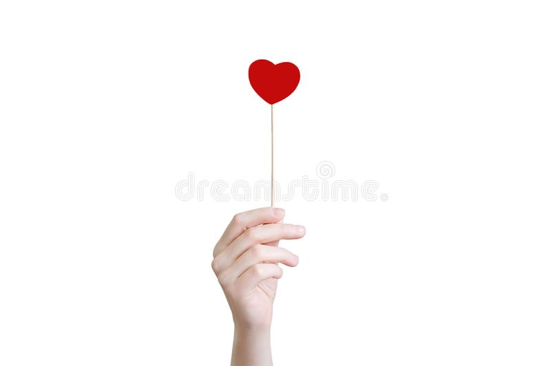 The girl holds in her hand a red heart on a stick. Close-up. royalty free stock photos