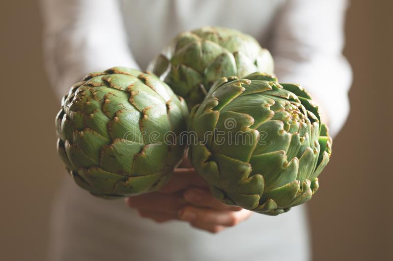The girl holds in her hands an artichoke with a blur of the background, the concept of proper and dietary nutrition, dottex. Horizontal picture royalty free stock image