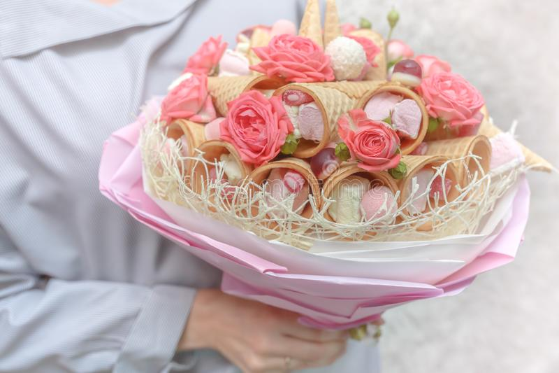 Girl holds in her hands a beautiful bouquet consisting of pink flowers of a rose and various sweets as a gift royalty free stock photos