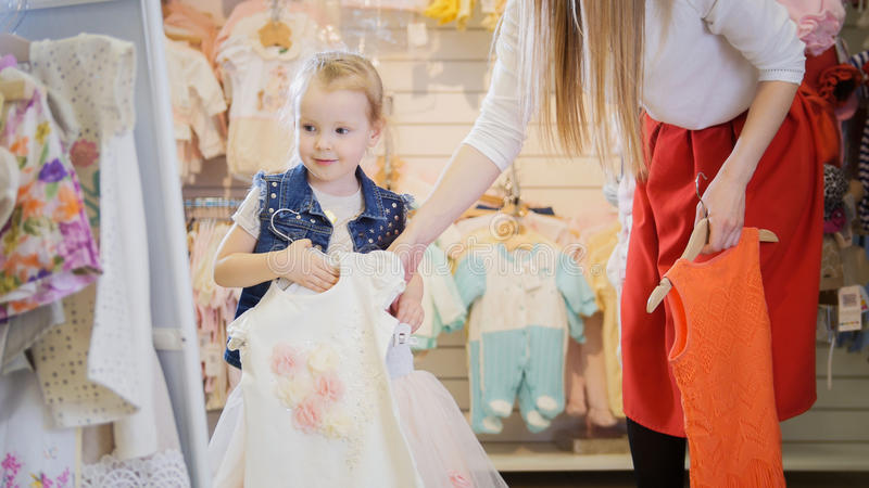 The girl holds in her hands hangers with dresses in front of a mirror in a children`s clothing store stock photo