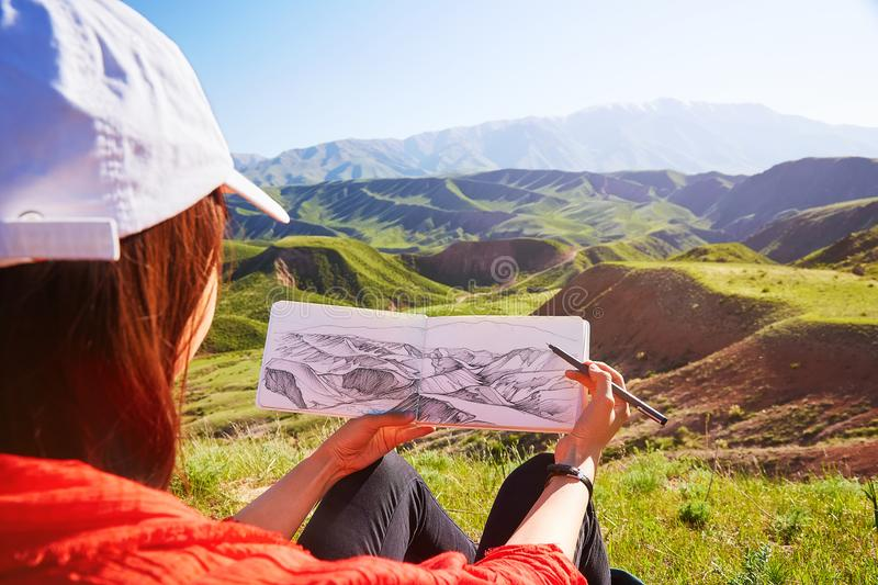 The girl holds in her hands a picture of a mountain landscape. Kazakhstan. Mountain spring landscape stock images