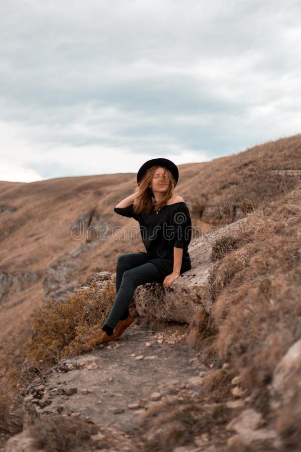 The girl holds her hat, turning her back to the valley with the mountains. sit on rock stock photography