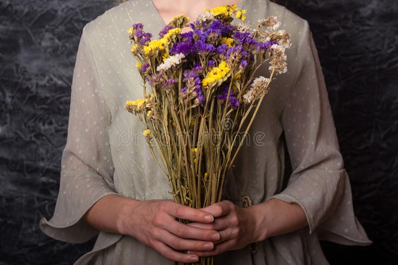 Girl holds immortelle flowers. A girl in a beautiful, vintage dress holds a bouquet of dried flowers in her hands. Dramatic photo. Immortelle Flowers. Dark royalty free stock photos