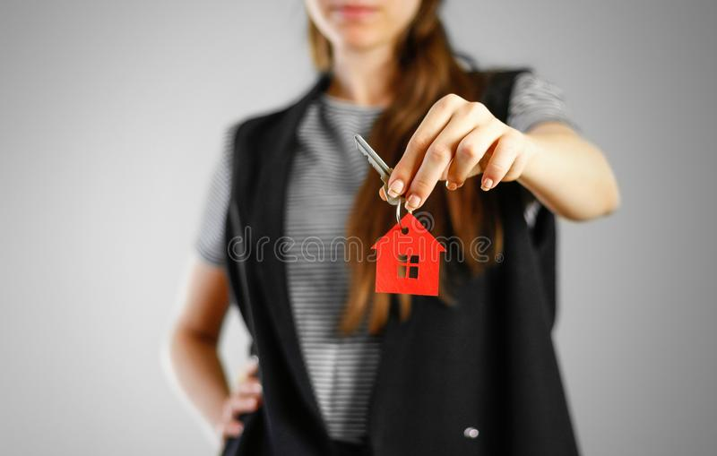 A girl holds the keys to the house. Key ring red house.  stock photography
