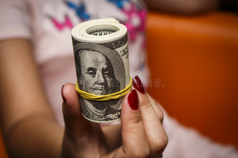 The girl holds a lot of bills. Of one hundred dollars royalty free stock photography