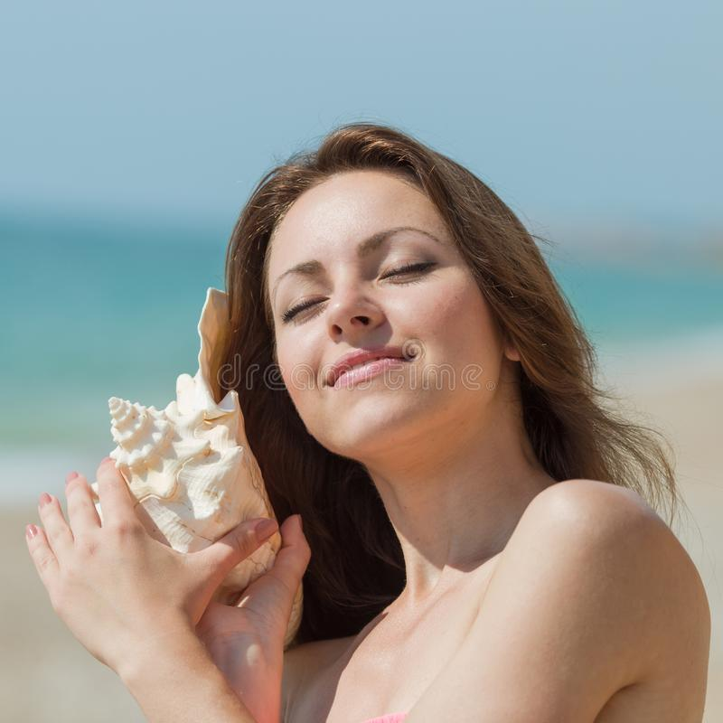 Girl holds mollusk shell and listens it with eyes closed. Portrait of slim girl with big shell of mollusk. Attractive young woman holds shell of mollusk and stock images
