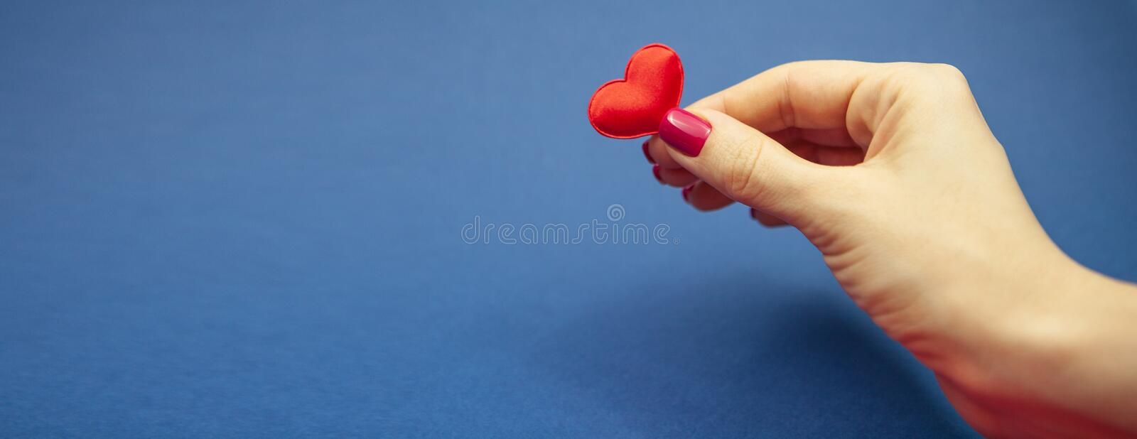A girl holds one heart on a blue background. Valentine`s Day and March 8 stock images